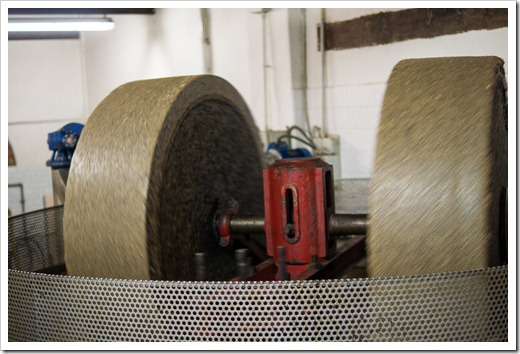 Large granite wheels are used to grind the olives, pits and all, into a very fine paste.  These wheels go round-and-round as olives are slowly added.