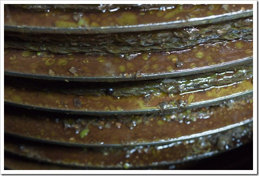 The olive mash is layered between the mats into a tall stack on a pressing spindle.