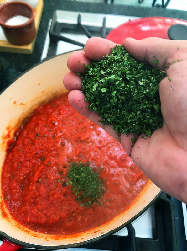 Adding the chopped oregano to the sauce